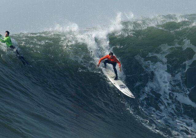 Chris Bertish, à direita, da África do Sul, cai em uma onda gigante ao lado de Kenny Collins, à esquerda, que realiza a manobra na final da competição de surf Mavericks, sábado, 13 de fevereiro de 2010, Half Moon Bay, Califórnia. Bertish venceu o torneio