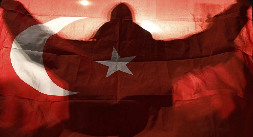 Um manifestante segura uma bandeira turca fora do consulado turco em Roterdã, onde uma multidão reuniu-se para aguardar a chegada da ministra da Família Turca, Fatma Betul Sayan Kaya.