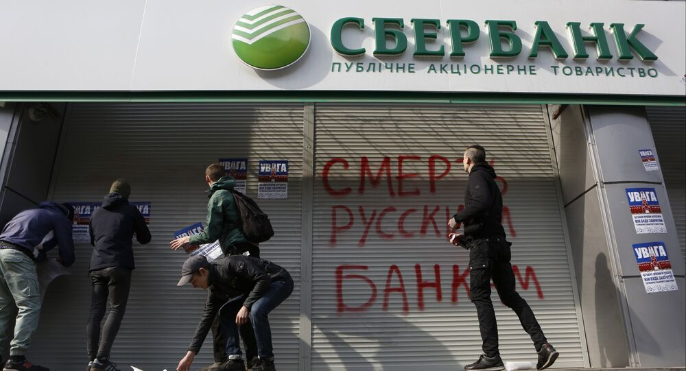 Radicals in front of a Sberbank branch in Kiev, putting up posters which read Attention! This is a bank of an aggressor country. It will be closed. Urgently withdraw your money!, during a protest. Graffiti reads Death to Russian banks. March 10, 2017