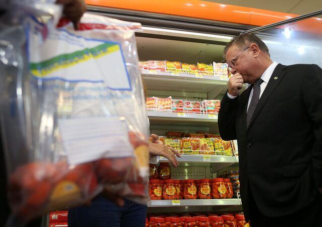 O ministro da Agricultura do Brasil, Blairo Maggi, inspeciona salsichas em um supermercado em Brasília, Brasil