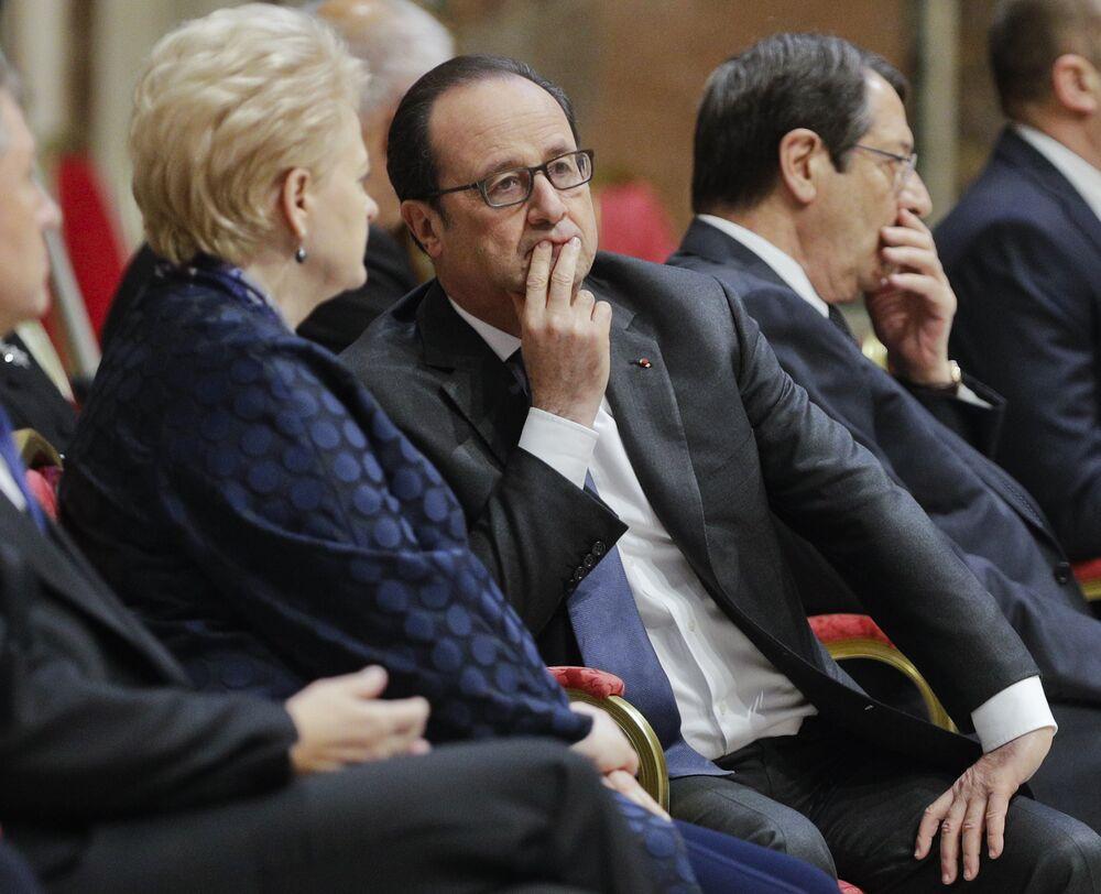 O presidente francês, François Hollande, conversa com a presidente da Lituânia, Dalia Grybauskaite, enquanto aguarda a chegada do pontífice