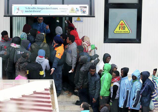 Imigrantes esperam assistência em frente à enfermaria do centro de imigração no sul da Itália, ilha de Lampedusa.