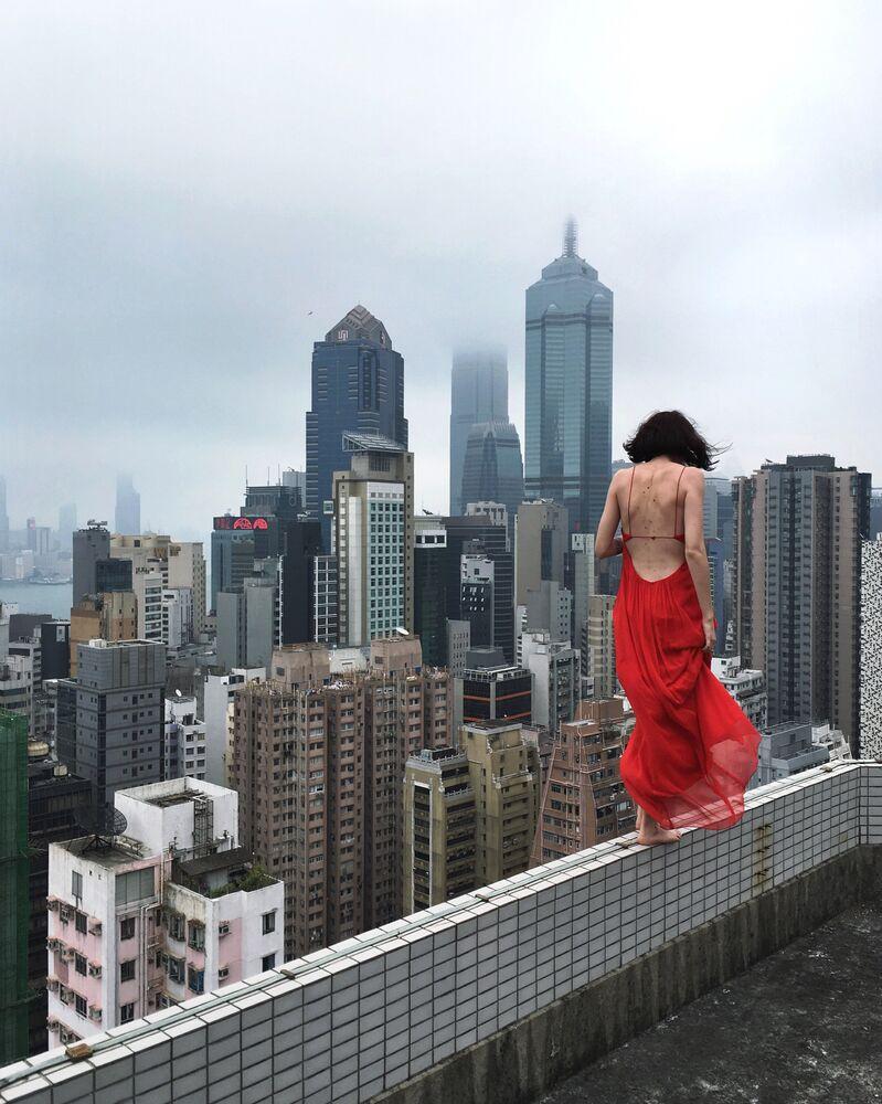 Rita Ahundova posa em frente da câmera no telhado de um edifício em Hong Kong. A maioria das fotografias do projeto são tiradas pela própria Rita usando seu iPhone com ajuda de timer ou controle remoto