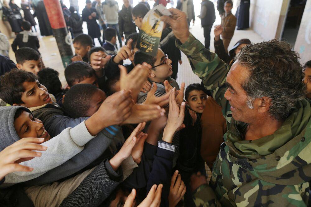 Membro do Exército Nacional da Líbia distribui panfletos a estudantes durante um curso destinado a alertá-los sobre minas e explosivos em Beghazi, Líbia, março de 2017.