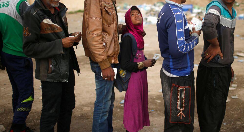 Iraquianos estão na fila para receber recursos alimentícios durante o combate das forças do Iraque com o Daesh, em Mossul ocidental, Iraque, março de 2017
