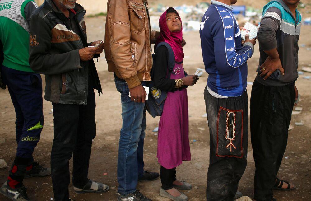 Iraquianos estão na fila para receber recursos alimentícios durante o combate das forças do Iraque com o Daesh, em Mossul ocidental, Iraque, março de 2017.