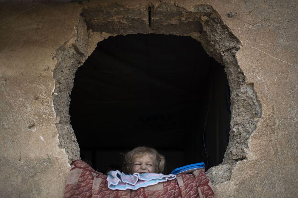 Criança iraquiana, que fugiu dos combates em Mossul, olha através da janela no campo para pessoas deslocadas internamente de Hassan Sham, no leste de Mossul, Iraque, novembro de 2016