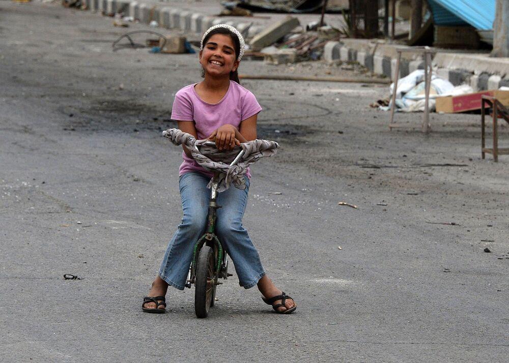 Uma criança anda de bicicleta numa das ruas de Palmira