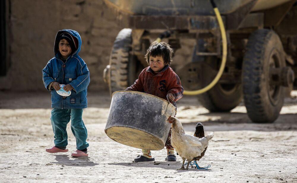 Crianças sírias de Waset Hashm, pequena povoação no leste de Raqqa, ajudam os parentes a recolher seus bens no momento em que os residentes da área se preparam abandonar suas casas, fevereiro de 2017