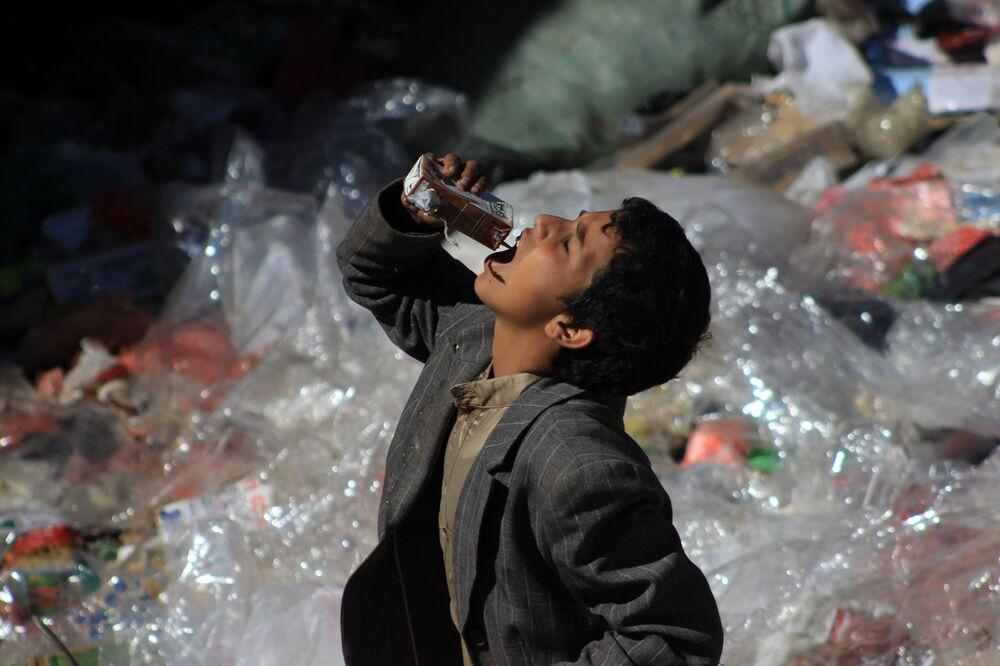 Rapaz iemenita bebe diretamente da embalagem recolhendo coisas do lixo em Saná, novembro de 2016