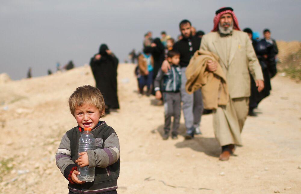 Rapaz iraquiano chora fugindo de Mossul durante a batalha das forças do Iraque com os militantes do Daesh em Mossul ocidental, no Iraque, março de 2017