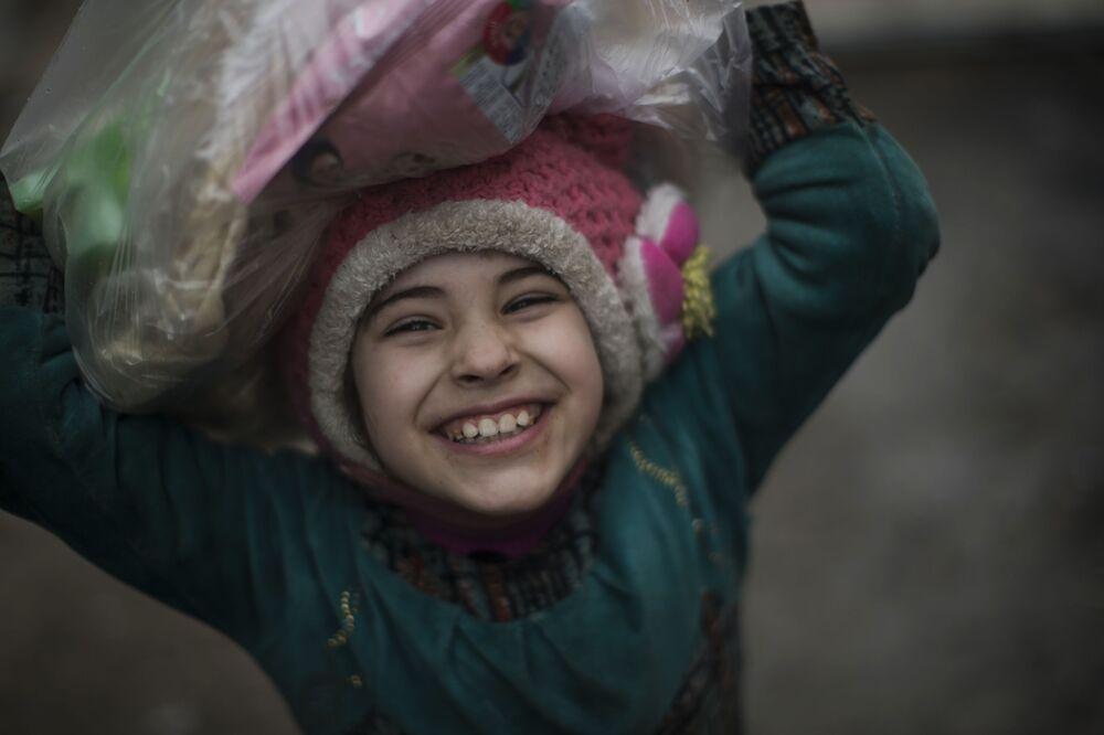 Criança iraquiana sorri após receber recursos alimentares das forças de segurança do Iraque perto da linha da frente, durante o combate contra o Daesh em Mossul ocidental, Iraque, março de 2017.