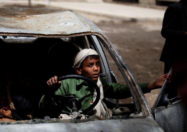 Rapaz em carro abandonado no orfanato em Saná, Iêmen