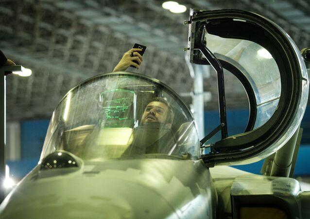 Homem tira selfie dentro do cockpit do caça Gripen E durante a feira LAAD 2017 no Rio de Janeiro