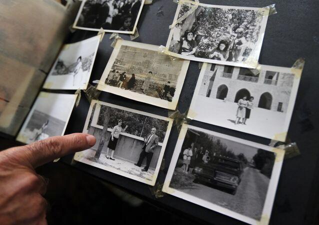 Khatchik Bakalian, um libanês armênio de 73 anos cujos pais fugiram do genocídio de armênios sob o Império Otomano em 1915, aponta para uma foto de seus pais no álbum de família