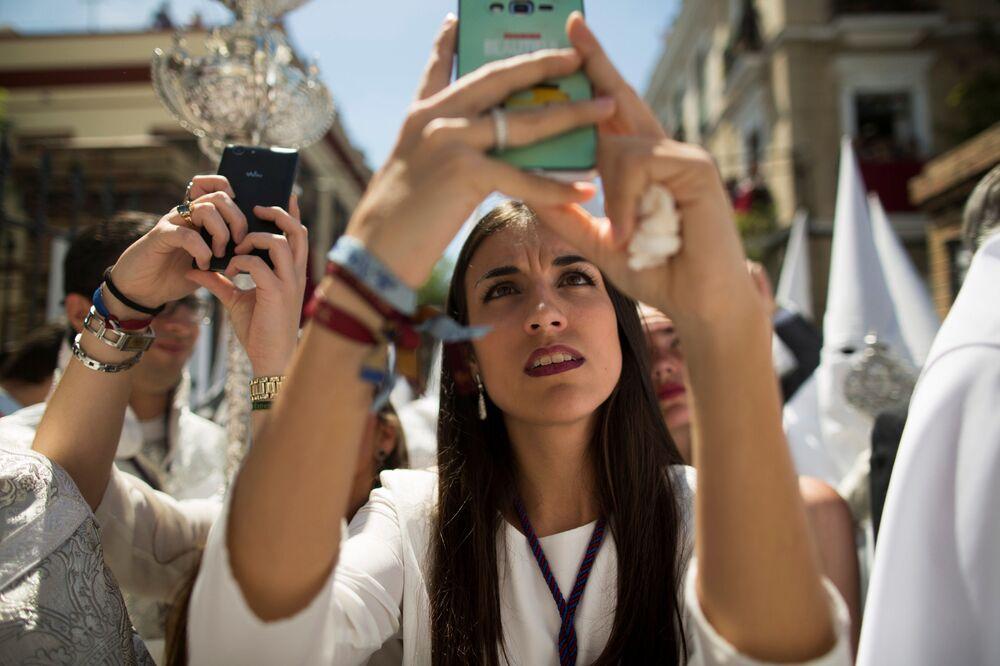 Moça tira fotografias da procissão durante a Semana Santa em Sevilha