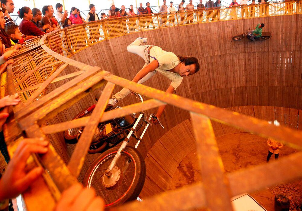 Motociclista em Poço da Morte durante uma feira no Nepal