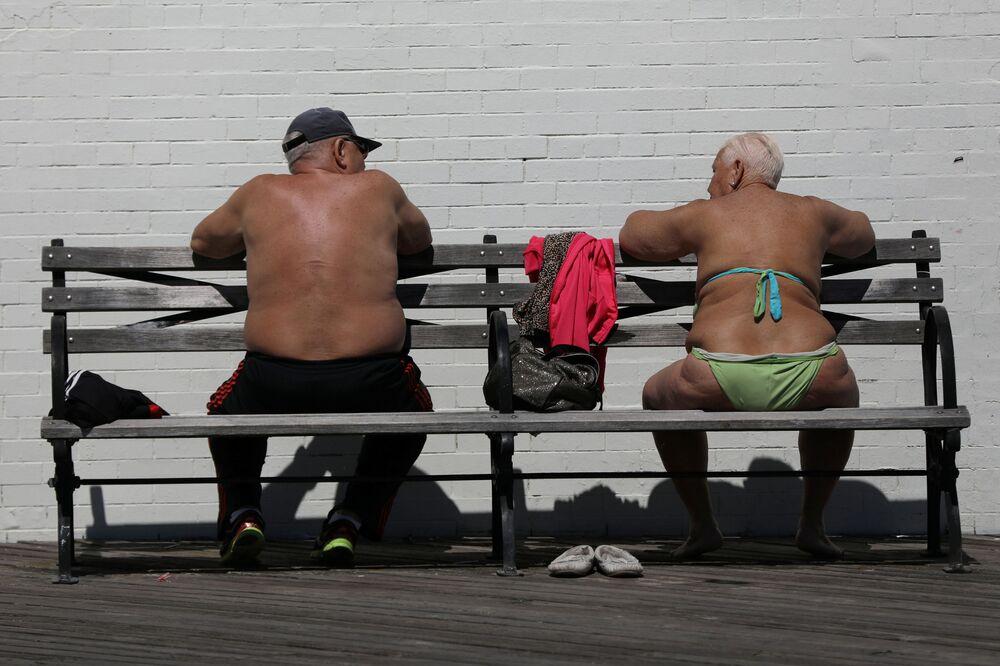 Residentes de Brooklin, nos EUA, tomam banhos de sol nos primeiros dias quentes