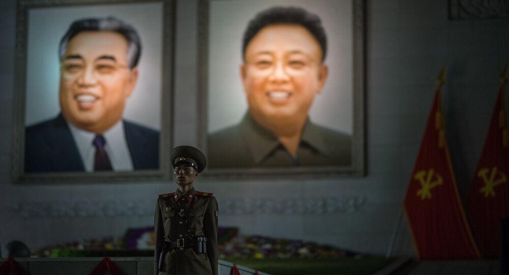 Um militar norte-coreano faz guarda de honor na frente de retratos de Kim Il-sung e Kim Jong-il durante os festejos em comemoração do 105 aniversário do nascimento do fundador do Estado da Coreia do Norte em Pyongyang