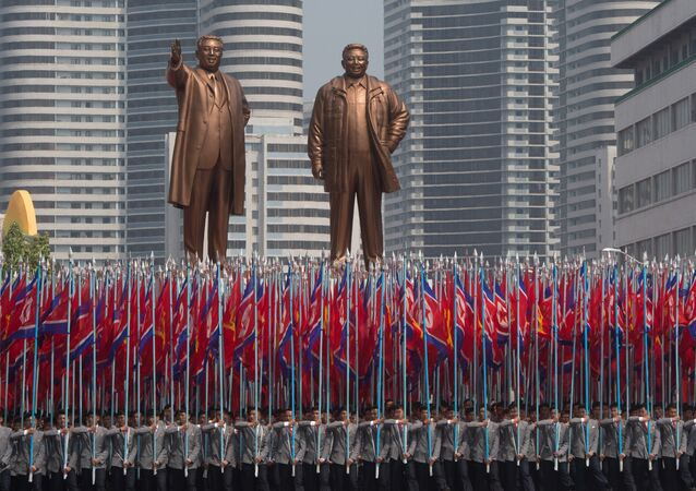 Participantes dos festejos comemorando os 105 anos de nascimento de Kim Jong-il são vistos com bandeiras na praça principal em Pyongyang