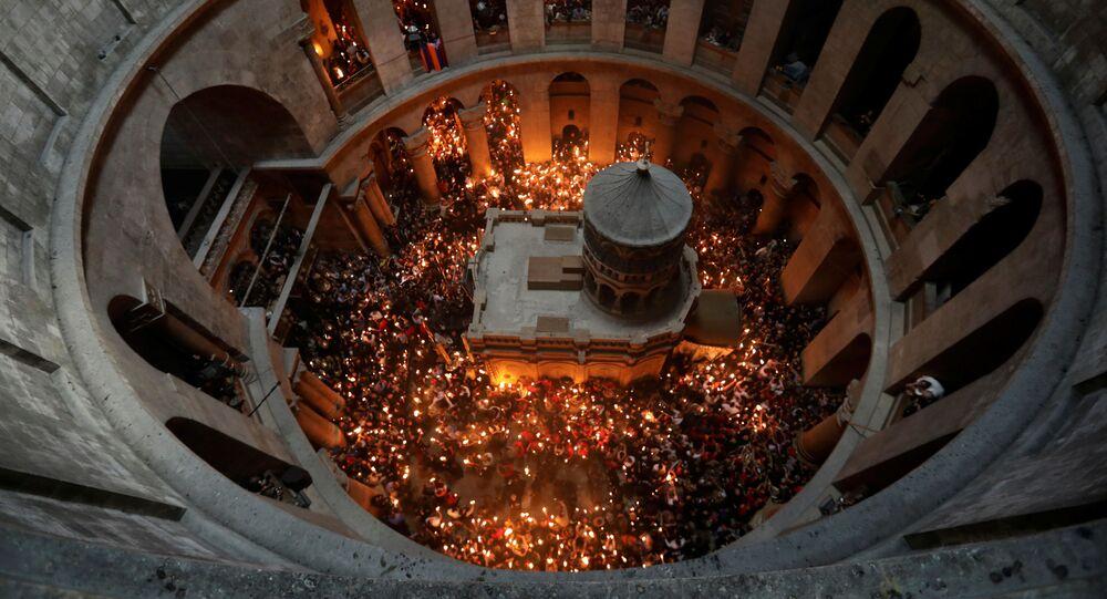 Fiéis com velas durante o milagre do Fogo Sagrado na Igreja do Santo Sepulcro em Jerusalém