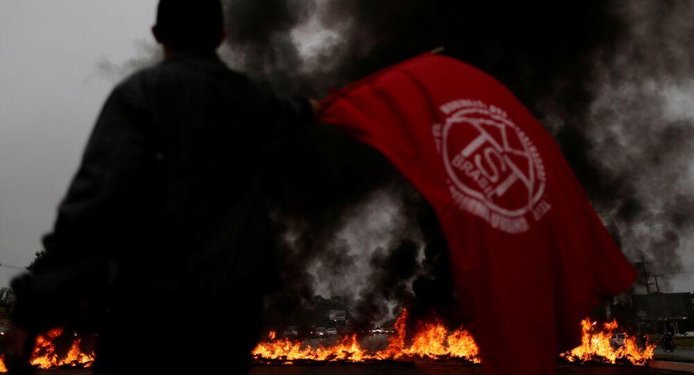 Um membro do MTST mostra a bandeira do movimento durante ato da greve geral de 28 de abril de 2017 em Brasília