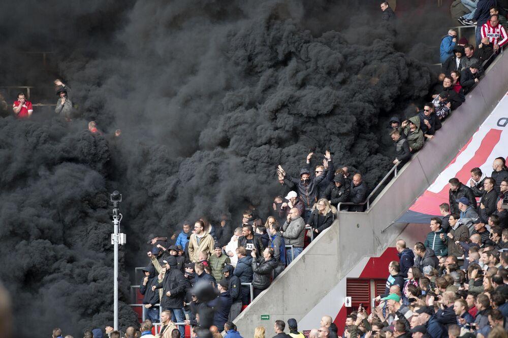 Fumaça negra cobre as tribunas durante jogo de futebol na cidade de Eindhoven, Holanda