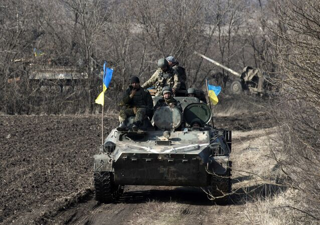 Ukrainian servicemen ride atop armored vehicle with a canon in tow and Ukrainian flags, near the village of Fedorivka, eastern Ukraine, Friday, Feb. 27, 2015