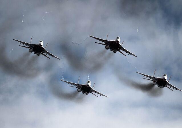 Os caças MiG-29 do grupo de pilotagem Strizhi no céu do aeroporto militar de Kubinka.