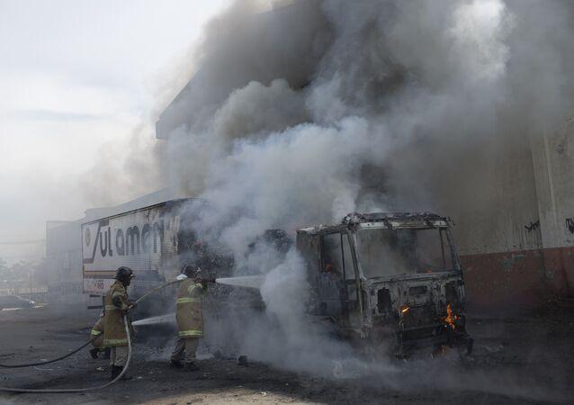 Bombeiros trabalham contra as chamas em caminhão incendiado por bandidos