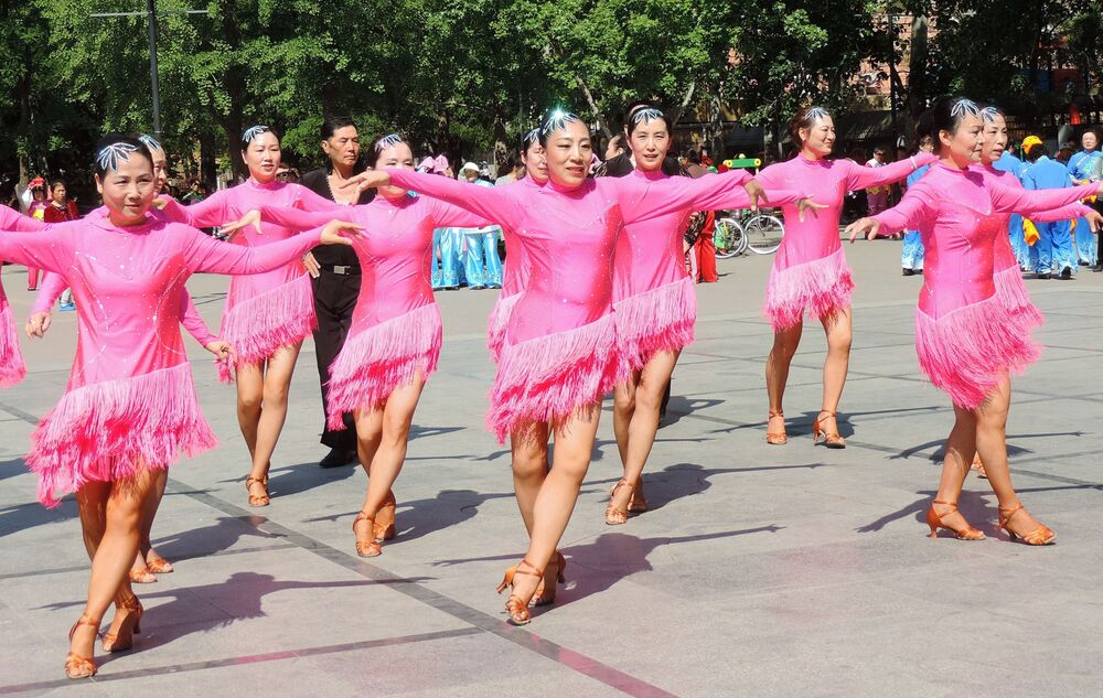 Chineses se divertem dançando em uma praça de Pequim