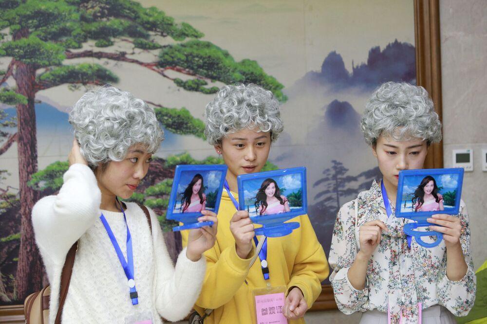 Jovens chinesas experimentam itens de uma funerária em Chongqing