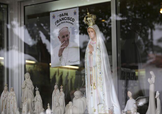 Nesta foto de 4 de maio de 2017, uma imagem mostrando Papa Francisco é vista na vitrine de uma loja que vende estátuas da Nossa Senhora de Fátima na cidade portuguesa de Fátima
