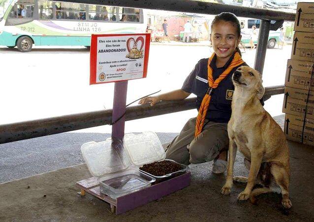 Giovanna Gabriely Santana de Lima com um dos cães abandonados alimentados por ela em Jaboatão dos Guararapes (PE)