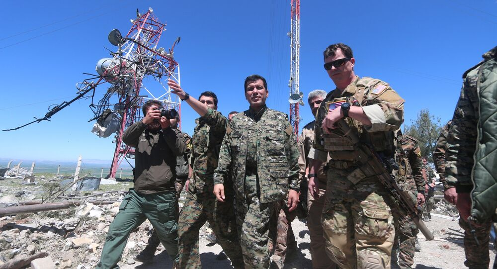 US military commander (R) walks with a commander (C) from the Kurdish People's Protection Units (YPG) as they inspect the damage at YPG headquarters after it was hit by Turkish airstrikes in Mount Karachok near Malikiya, Syria April 25, 2017.