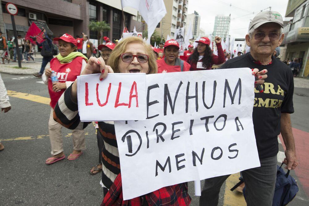 Senhora exibe cartazes em defesa de Lula e dos direitos dos cidadãos em Curitiba