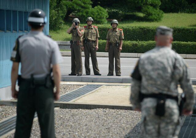 Soldados norte-coreanos tiram fotos de soldado sul-coreano e  de militar norte-americano junto à linha de demarcação que separa as duas Coreias (foto de arquivo)