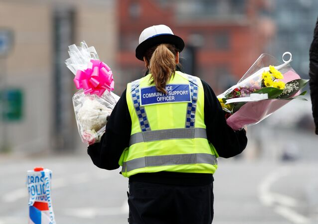 A community support officer carries flowers near Manchester Arena in Manchester, Britain May 24, 2017.