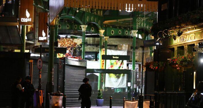 Oficial armado faz guarda em frente ao Borough Market, onde pelo menos duas pessoas foram esfaqueadas nesta madrugada em Londres.