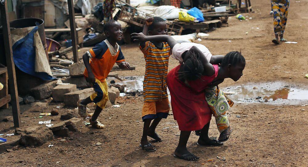 Nesta foto de 25 de novembro de 2014, crianças são vistas brincando no porto de Conakry, Guiné. Muitas pessoas morreram no país por causa da malária, que, segundo dados oficiais, ceifou mais vidas do que o ebola