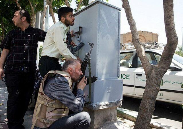 Membros das forças iranianas se escondem por detrás de uma parede durante o ataque contra o parlamento do Irã no dia 7 de junho de 2017
