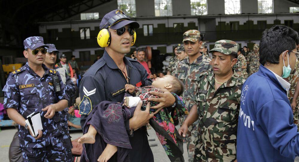 Um militar da Força Aérea da Índia socorre uma criança no Nepal.