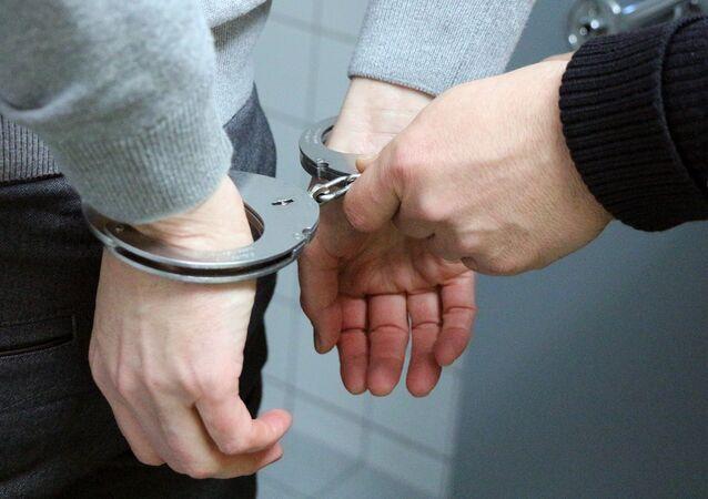 Imagem de um homem sendo algemado pela polícia