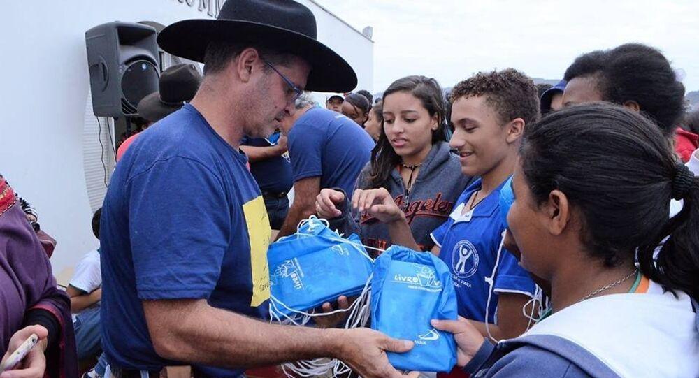 Neto do arquiteto Oscar Niemeyer, Carlos Oscar Niemeyer Magalhães entrega livros durante um dos eventos da Cavalgada da Cultura