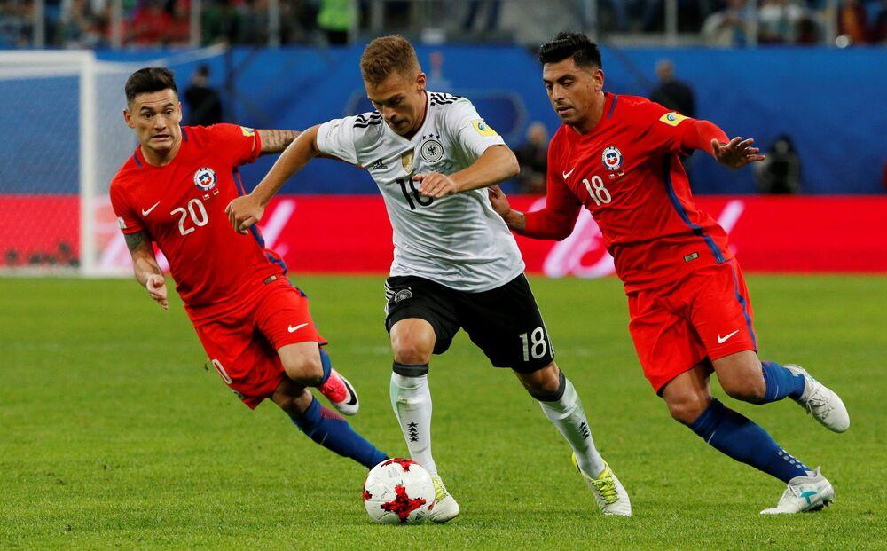 O alemão Joshua Kimmich disputa a bola com dois chilenos
