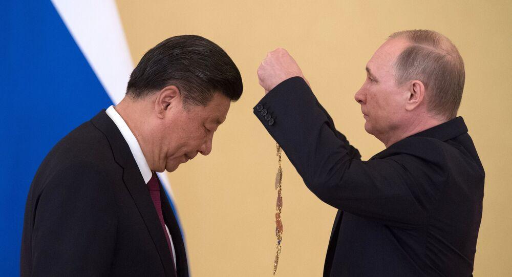 Xi Jinping se inclina para receber a ordem de Santo André Apóstolo Protocletos das mãos de Vladimir Putin, em 4 de julho de 2017