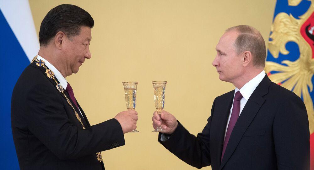 Xi Jinping e Vladimir Putin tomam brindam uma copa de champanhe durante o encontro em Moscou, em 4 de julho de 2017