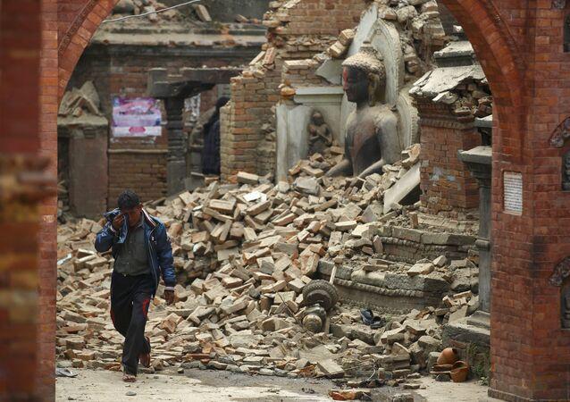 Homem chora enquanto passa ao lado de uma estátua de Buda danificada pelo terremoto no Nepal