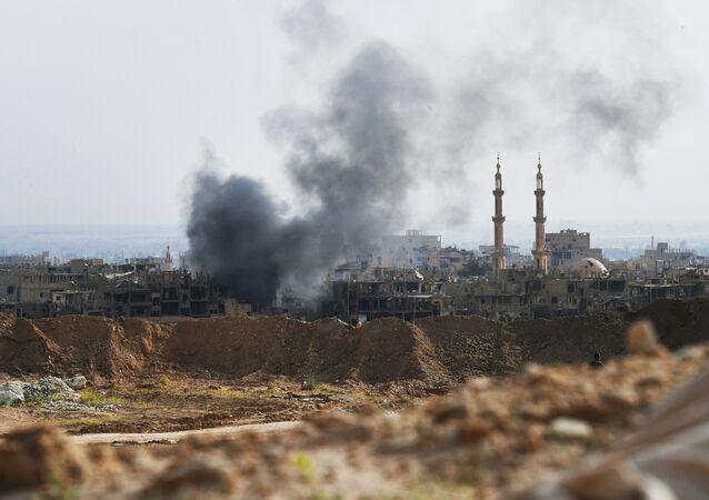 Fumaça se levanta sobre a cidade síria de Deir ez-Zor após ataques aéreos da coalizão internacional liderada pelos EUA (arquivo)