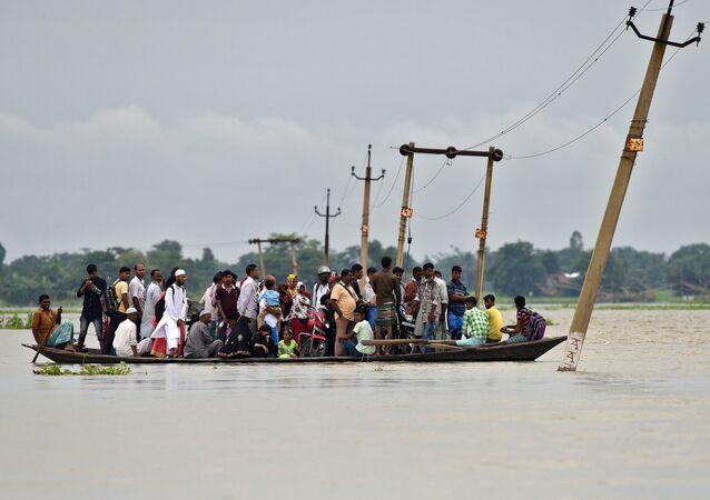 Moradores da povoação de Asigarh atravessam caminho inundado no estado de Assam, Índia